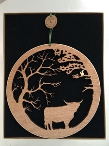 Wooden wall hanging of a highland cow under two trees and a squirrel in the branches