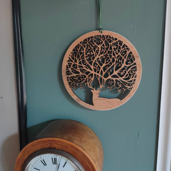 Wooden wall ornament hanging above a clock of a stag with antlers that create branches of a tree