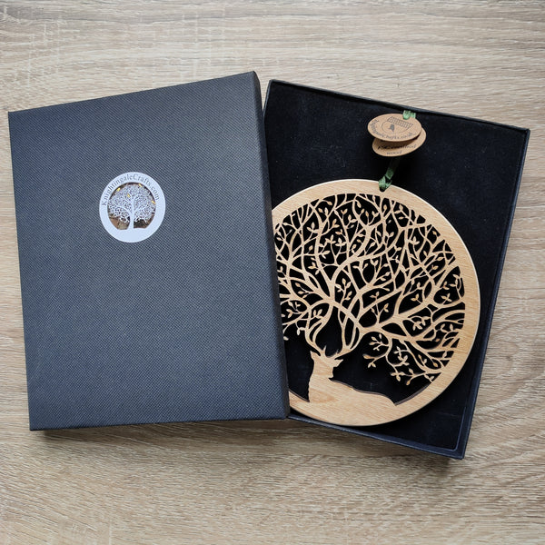 Wooden wall ornament of a stag in a gift box with antlers that create branches of a tree