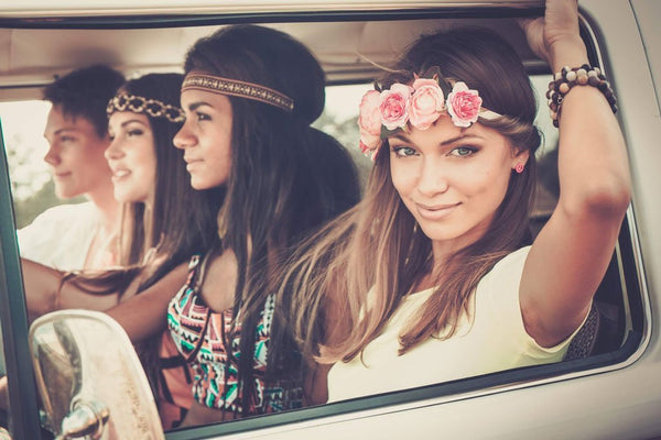 Beautiful friends travelling in a camper van wearing festival sixties style clothing