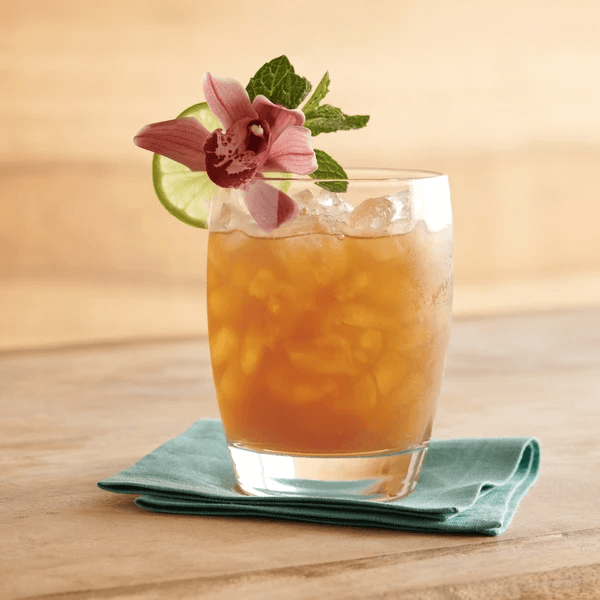 Ride or Die NA Mai Tai on ice with garnish of orchid, mint, and lime.