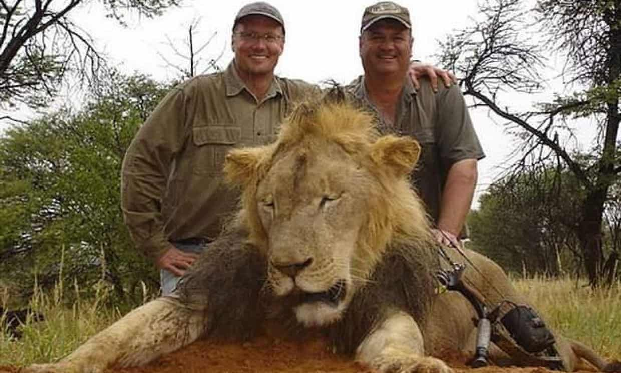 Hunters posing with a lion.