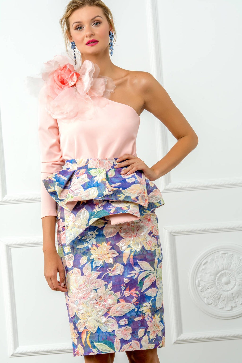 Pencil skirt with large asymmetric ruffle at the waist in blue brocade fabric with coral pink flowers.