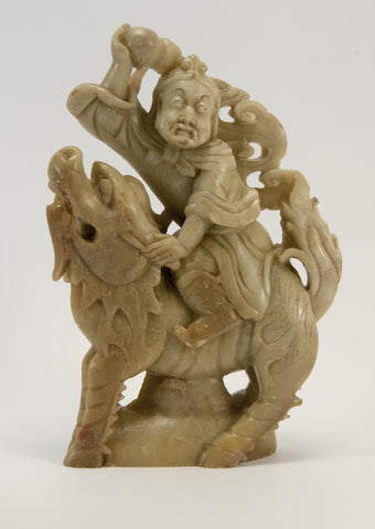 carved soapstone man sitting on dragon 010