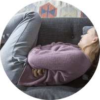 Woman in fetal position on sofa