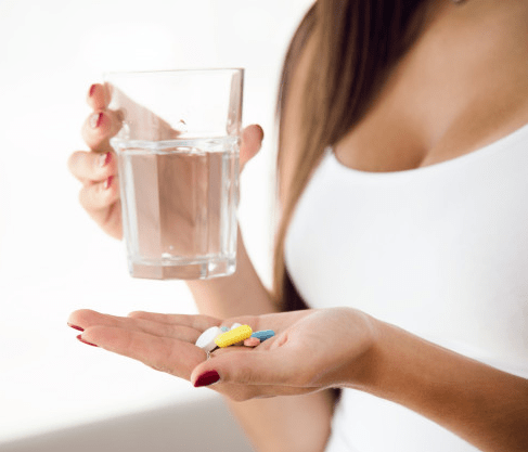 Woman holding a glass of water and colorful pills
