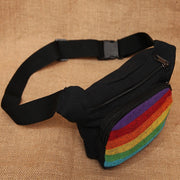 Rainbow Festival Bum Bag, mainly black with a front rainbow pannel, two zip pockets and adjustable waist strap