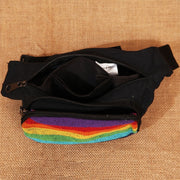 Rainbow Festival Bum Bag, mainly black with a front rainbow pannel, two zip pockets and adjustable waist strap, view with zips open.