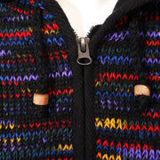 Close up of zip and toggles on zip up woollen hooded coat with fleece lining, overall colouring is black with rainbow streaks running through.