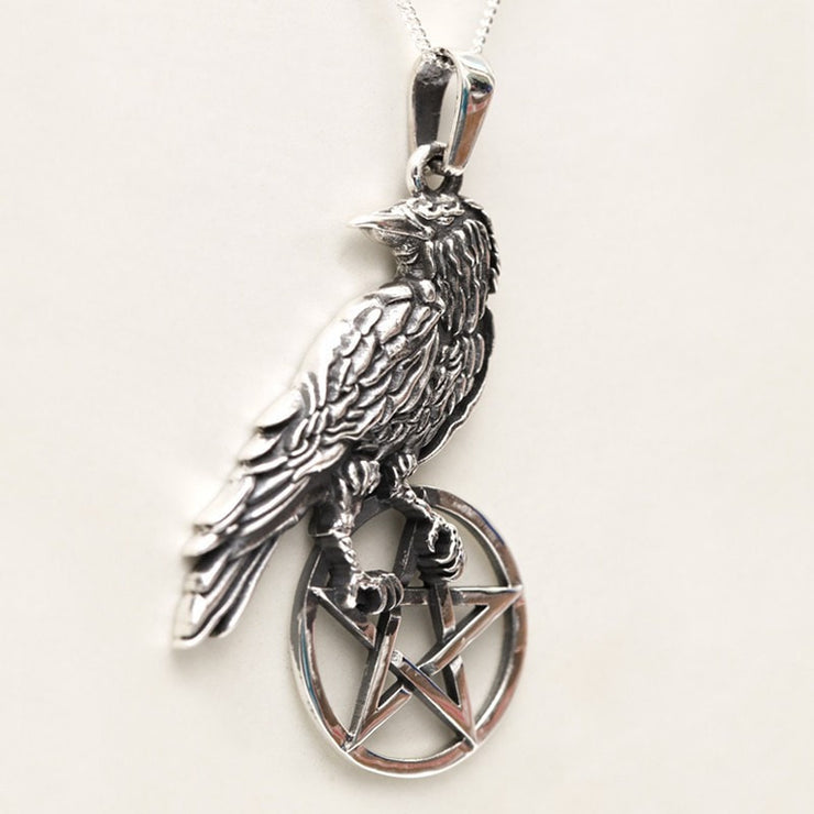 Raven bird sitting on a pentagram pendant silver