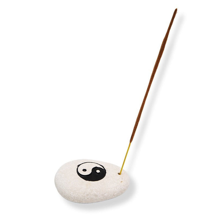 Stone incense holder with yin yang carved into top and painted and small hold drilled to one side to hold an incense stick - zoomed out view