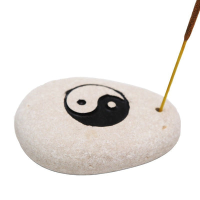 Stone incense holder with yin yang carved into top and painted and small hold drilled to one side to hold an incense stick