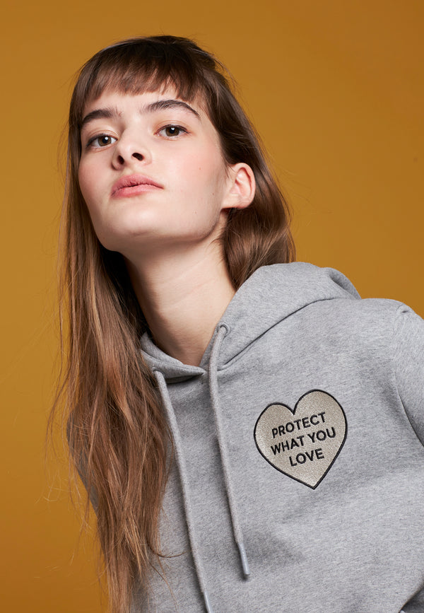 Model trägt PROTECT WHAT YOU LOVE Hoodie von PHYNE in grau