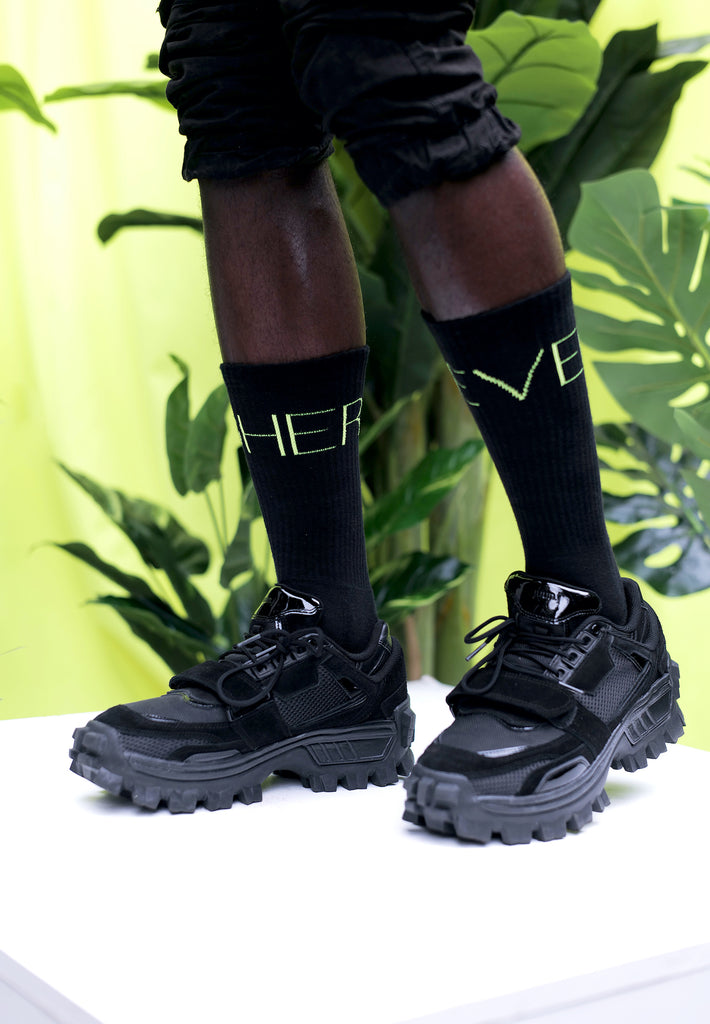 "[""Model trägt Higher Level Tennis Socken in schwarz by Nikeata Thompson""]"