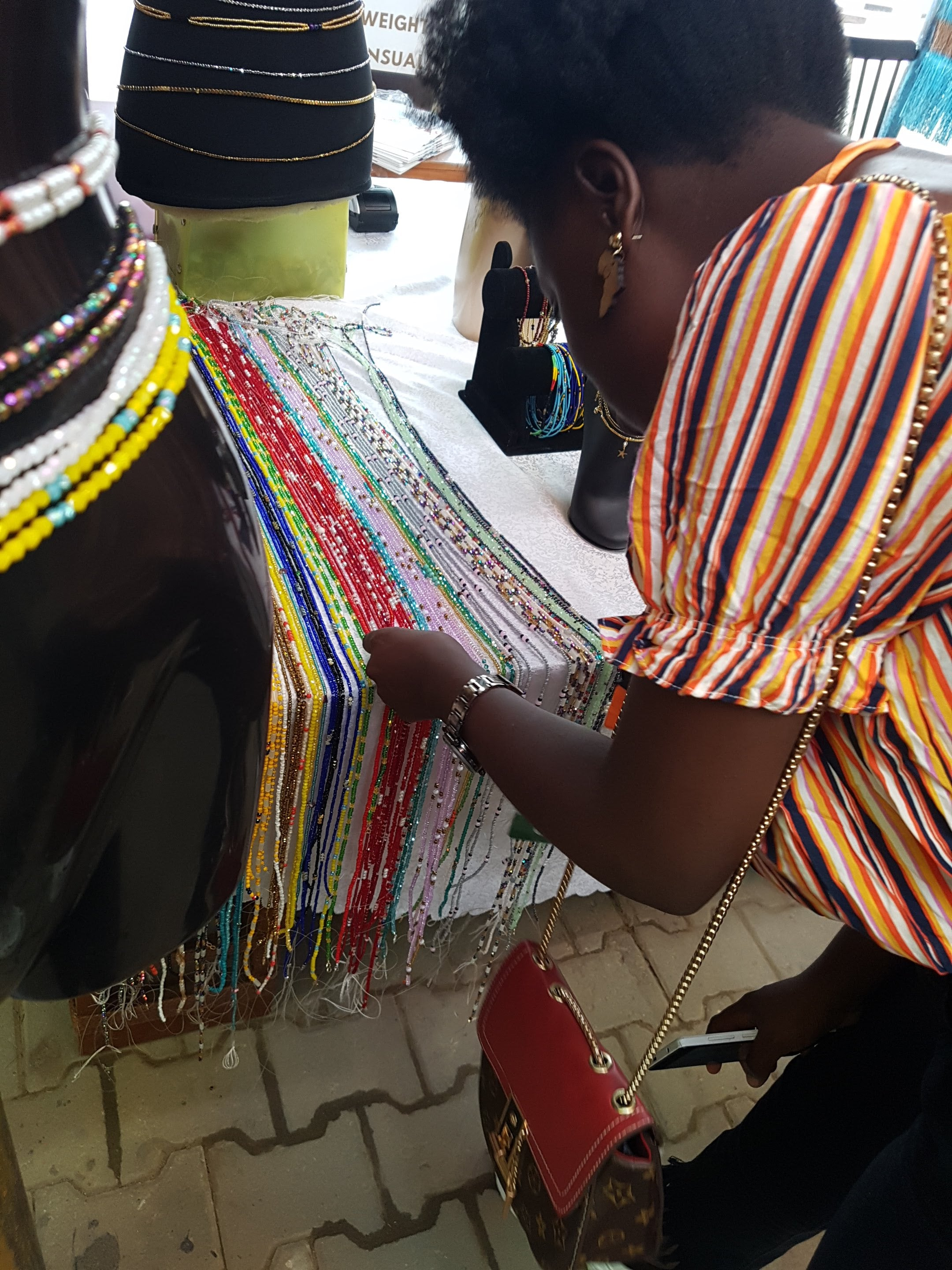 Black Woman Choosing Waist Beads Of Different Colours Lined Up On A Table