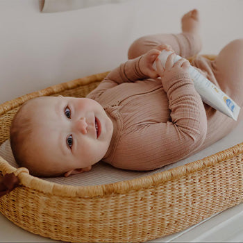 10 month old baby in a diaper changing basket