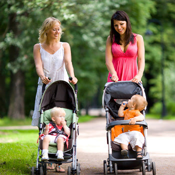 Two moms on a stroller walk with their 11 month old babies