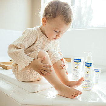 Baby taking a bath with Mustela bath products