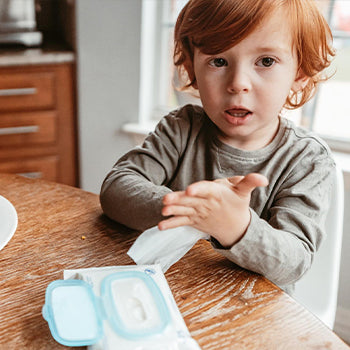 Child cleaning his hands after eating