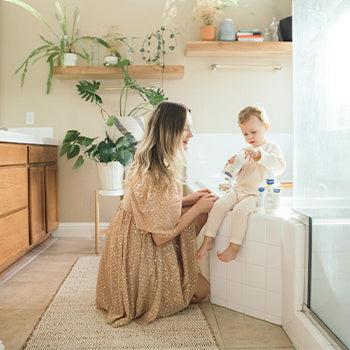 Mom caring for her 1 year old baby in the bathroom