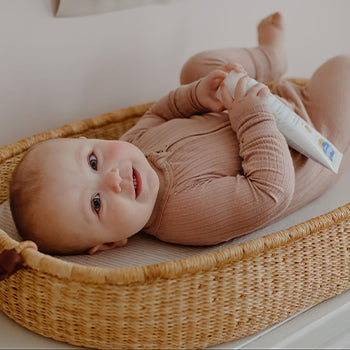 2 month old baby holding mustela baby product