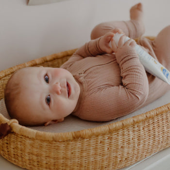 4 month old baby laying down with baby products