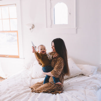Mom holding 5 Month Old Baby on her bed