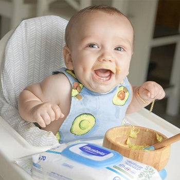 5 Month Old Baby eating food at high chair