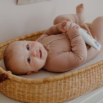 6 month old baby laying down on back holding Mustela products