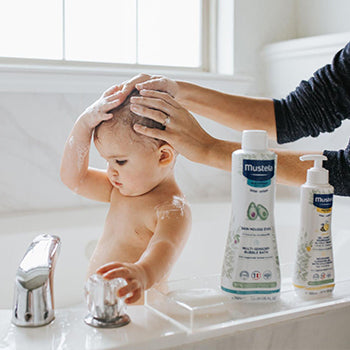Parent washing hair of her  7 month old baby