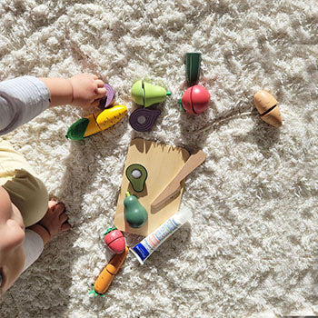 9 month old baby playing with plastic fruit toys