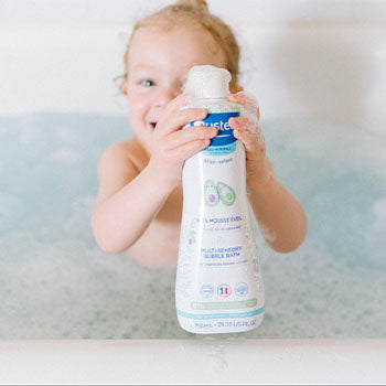 9 month old baby taking a bath with mustela bubble bath