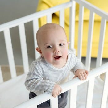 baby standing and looking upwards from inside his crib