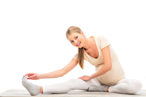 Pregnant woman stretching to help with aching legs during pregnancy