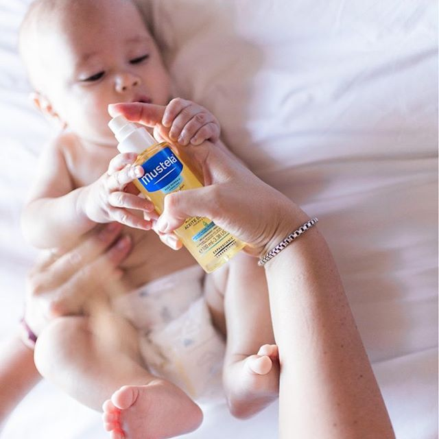 Parents putting Mustela's baby oil on baby