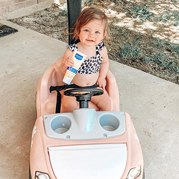 baby driving around in toy car holding Mustela baby products