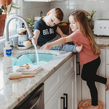 two kids washing hands to prevent the baby flu