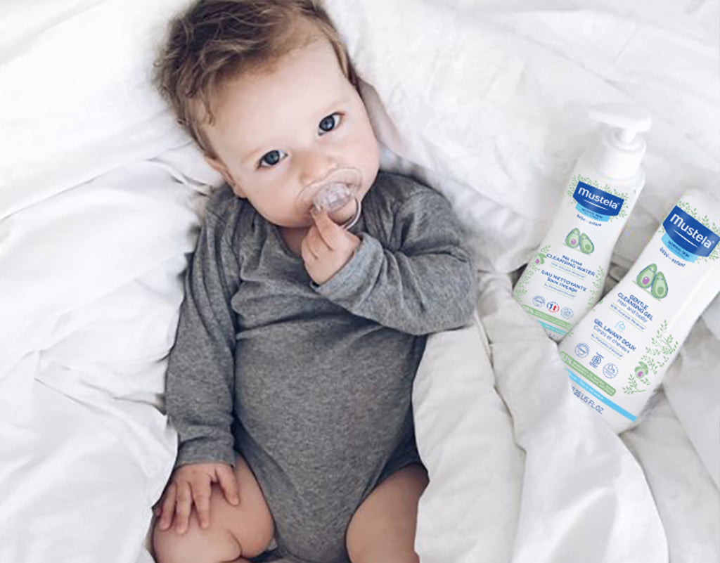 Baby laying next to Mustela baby products