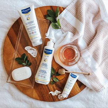 Mustela baby products on a wood round tray on bed