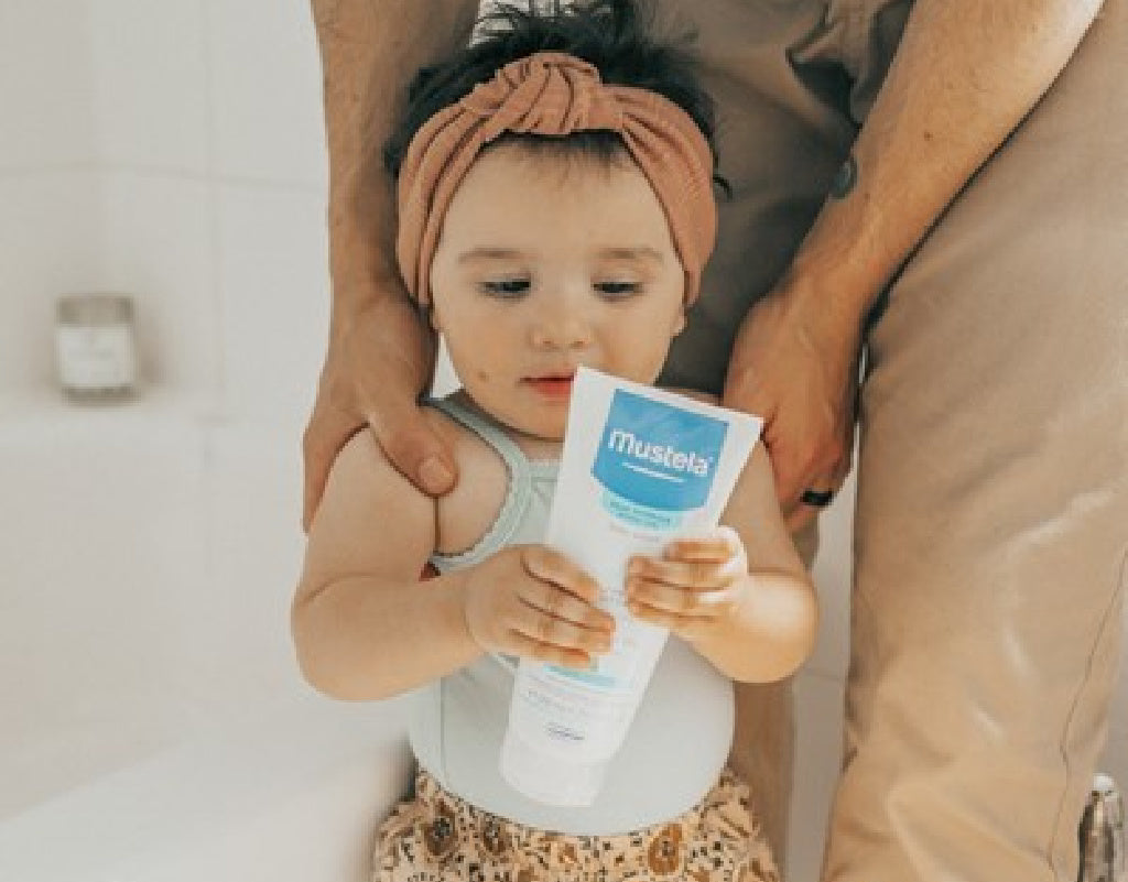 Baby holding Mustela skin care product