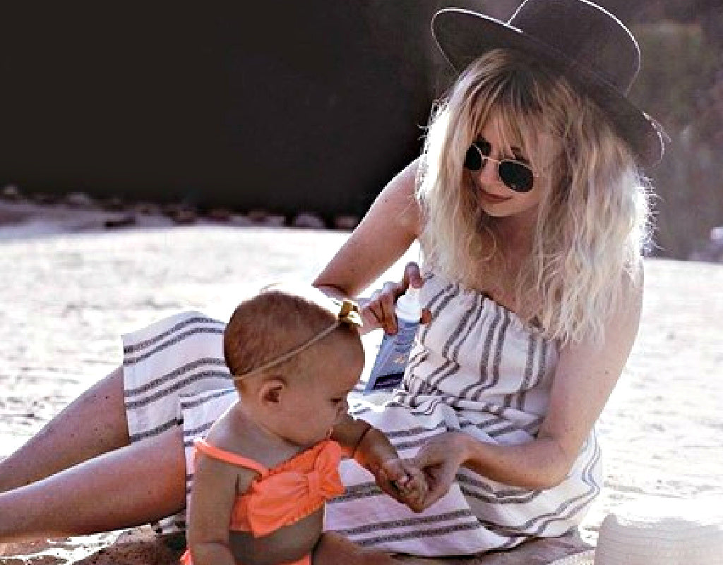 Mom apply sunscreen on child for baby safety