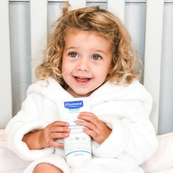 young girl holding  Mustela's Stelatopia Emollient Cream for her Childhood Eczema