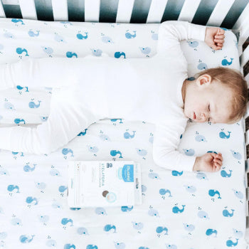 young kid with childhood eczema sleeping in a crib