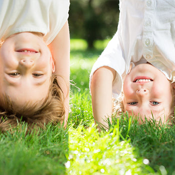 Two kids doing headstands on the grass