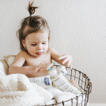 kid sitting in a basket filled with products to help with Childhood Eczema