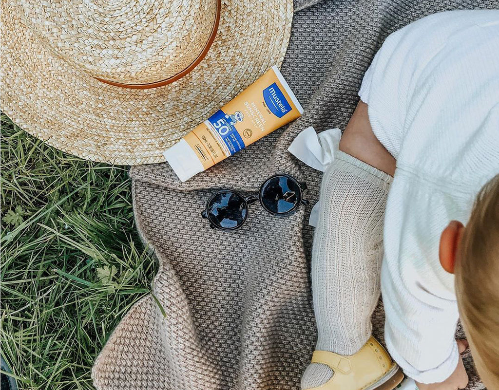 Mustela daily sunscreen next to child on blanket
