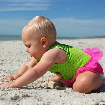 10 month old baby in pink and green bathing suit playing in the sand on the beach