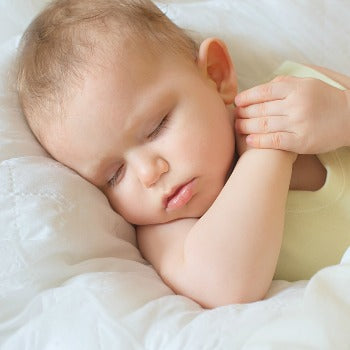 baby sleeping on her back with hands clasped together