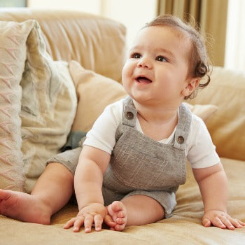 smiling baby in overalls sitting on beige sofa