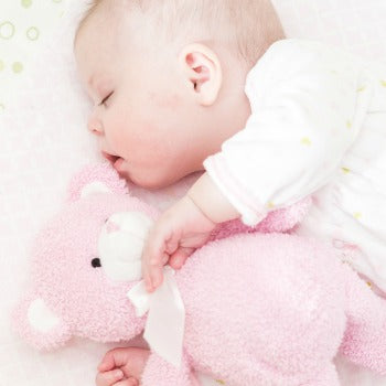 baby sleeping on her side with pink teddy bear